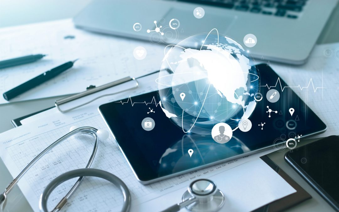 A tablet with a digital globe and healthcare information technology icons next to a laptop, stethoscope, and paper.