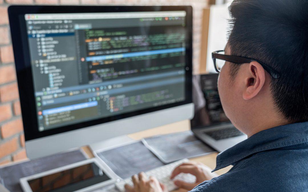 programmer writing code into a web development framework on his computer