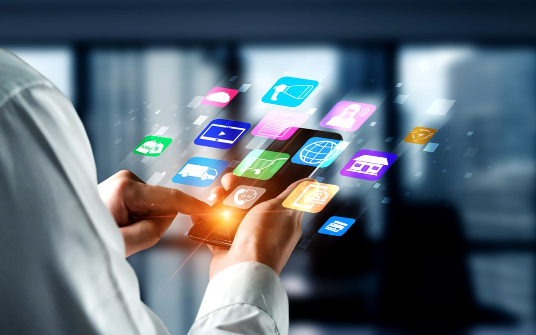 A person wearing a white long-sleeved shirt is holding a smartphone with projected images of business application icons.